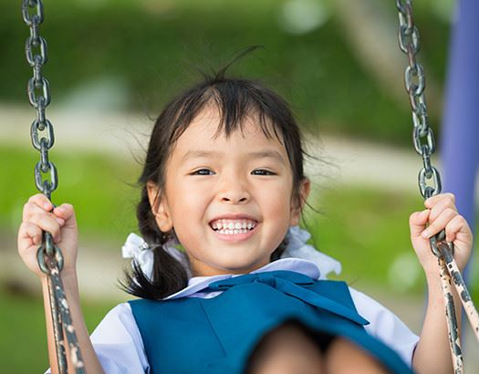 Young girl smiling while swinging