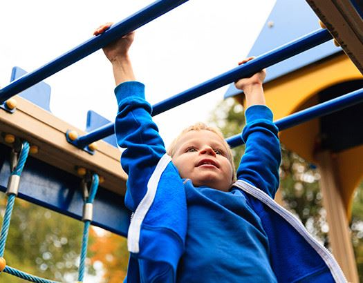 Young boy in jacket swinging on the monkey bars
